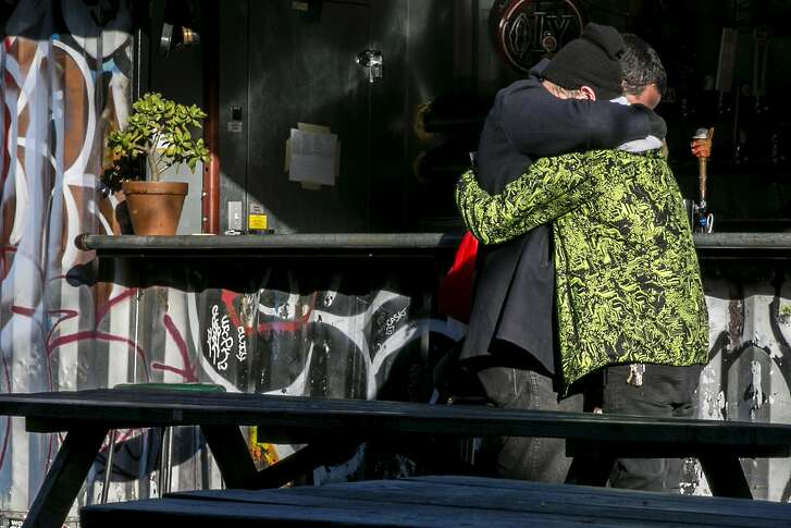 People embrace each other at Eli's Mile High Club bar, on Saturday, Dec. 3, 2016 in Oakland, Calif. At least nine people were killed in a warehouse party fire at 31st Avenue and International Boulevard, in the Fruitvale neighborhood. As many as 100 people were inside for a performance by the Golden Donna 100 Percent Silk touring electronic dance music show.