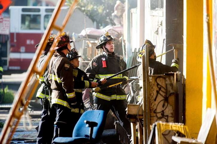 Firefighters work to clear rubble at the scene of a fire that killed at least nine people on 31st Avenue in Oakland, Calif., on Saturday, Dec. 3, 2016.