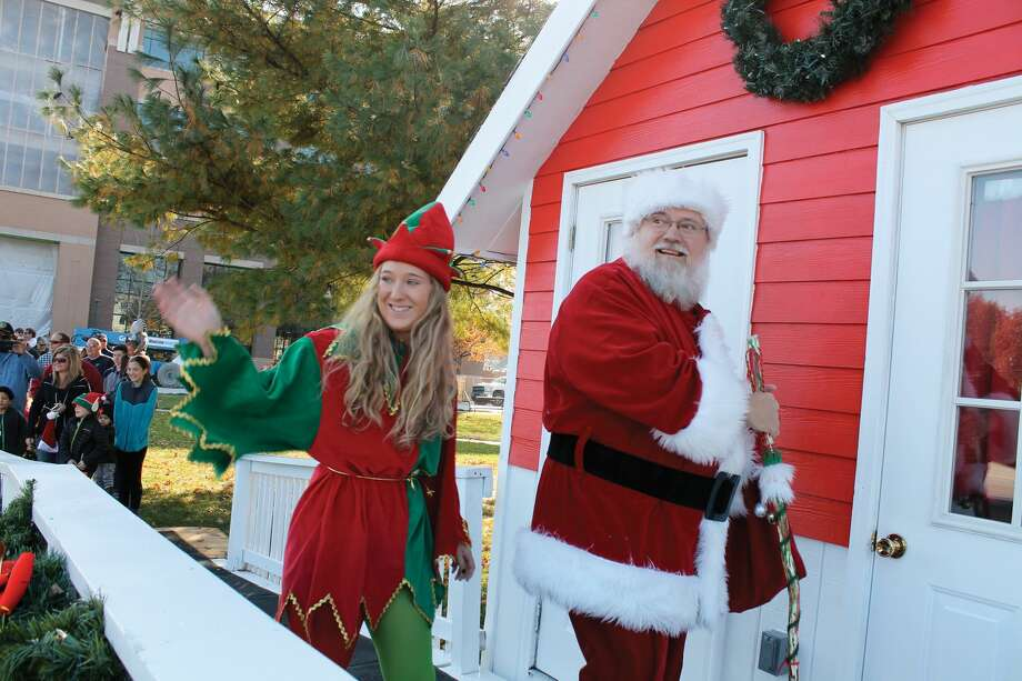 Santa Claus and his elf enter the City Park Santa House. Photo: Bill Tucker • Btucker@edwpub.net