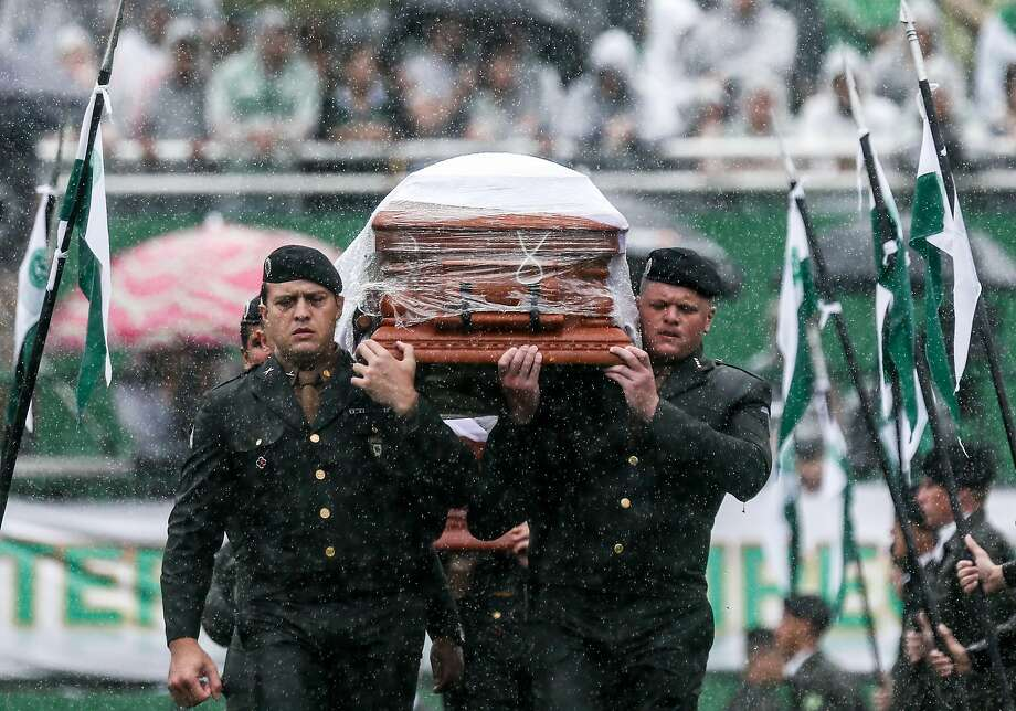 Soldiers carry the coffin of one of the crash victims at the Arena Conda stadium in Chapeco, Brazil. Photo: Buda Mendes, Getty Images