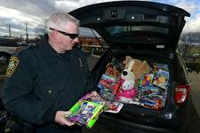 Lieutenant Terry Blake loads up his cruiser as The Norwalk Police Department holds a Stuff A Cruiser event to benefit needy children at Toys R Us on Connecticut Avenue in Norwalk, Conn. Friday, December 2, 2016. All toys collected will be donated to clients of the Domestic Violence Crisis Center.
