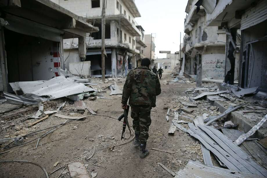 A Syrian soldier patrols newly captured terrain in the eastern Aleppo neighborhood of Tariq al-Bab. Photo: Hassan Ammar, Associated Press
