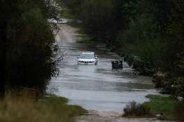 An SUV is left abandoned along Montego Street near Leon Valley after high water stalled the vehicle along the gravel road  on Saturday, Dec. 3, 2016. Downpours have kept rescue crews busy throughout the day as weather forecasts have called for continued rain storms in the area for the weekend.