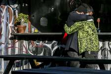 A man in the green sweater who only gave his name as John is embraced by a friend at Eli's Mile High Club bar on Saturday, Dec. 3, 2016 in Oakland, Calif. At least nine people were killed in a warehouse party fire at 31st Avenue and International Boulevard in Oakland's Fruitvale neighborhood. As many as 100 people were inside for a performance by the Golden Donna 100 Percent Silk touring electronic dance music show. John said he was one of the event organizers and a doorman at the warehouse when the fire broke out. He said he was distraught as he stood outside the burning building for hours unable to help people.
