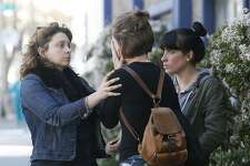 Women console each other while awaiting word on friends and family members at an Alameda County Sheriff's office in Oakland, Calif. on Saturday, Dec. 3, 2016, after at least nine people died and several others reported missing in an overnight fire.
