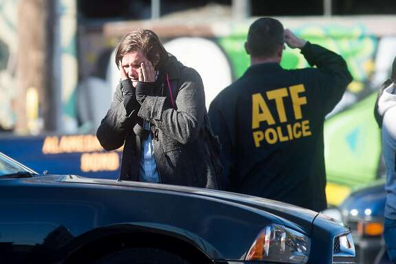 A man is overcome with emotion while speaking with emergency personnel at the scene of a fire that killed at least nine people in Oakland, Calif., on Saturday, Dec. 3, 2016.