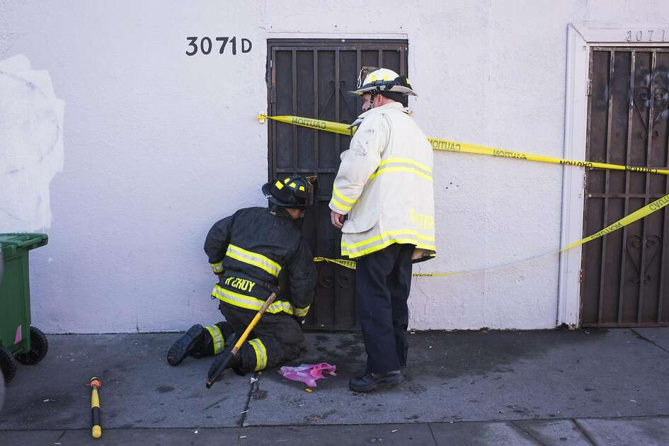 Firefighters close a door leading into a building that was the scene of a fire near 31st Avenue and International Boulevard on December 3, 2016 in Oakland, California