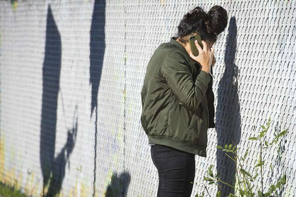 An onlooker cries while talking on her phone at the scene of a fire near 31st Avenue and International Boulevard on December 3, 2016 in Oakland, California