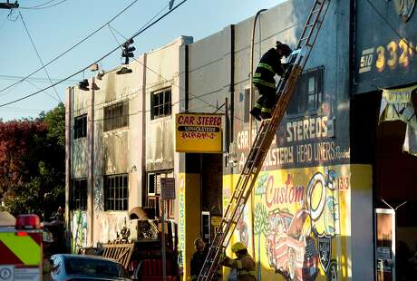 A firefighter climbs down a ladder at the scene of a fire that killed at least nine people on 31st St. in Oakland, Calif., on Saturday, Dec. 3, 2016.