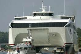 """**FILE** Spectators watch """"The Cat"""" ferry leave Rochester, N.Y., with a U.S. Coast Guard escort enroute to Toronto in this June 30, 2005, file photo. The giant car-and-passenger catamaran that zips across Lake Ontario at 50 miles an hour has been less than half-full during its first four weeks in service but its ridership is picking up, the operator said Monday, Aug. 1, 2005. (AP Photo/David Duprey)"""