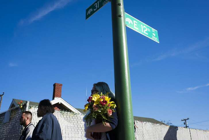 An onlooker holds flowers at the scene of a fire near 31st Avenue and International Boulevard on December 3, 2016 in Oakland, California