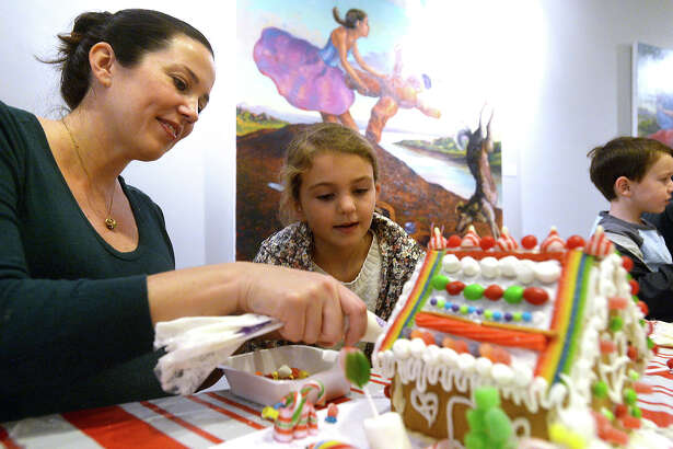 Erin Coco and daughter Lily Coco add decorative touches to their creation during the Holiday Gingerbread House Workshop held Saturday morning at the Art Museum of Southeast Texas. Families and individuals put their creativity and holiday spirit together to create the houses, which were made from fresh gingerbread components and a variety of colorful candies, marshmallows, and frosting.  Photo taken Saturday, December 3, 2016 Kim Brent/The Enterprise