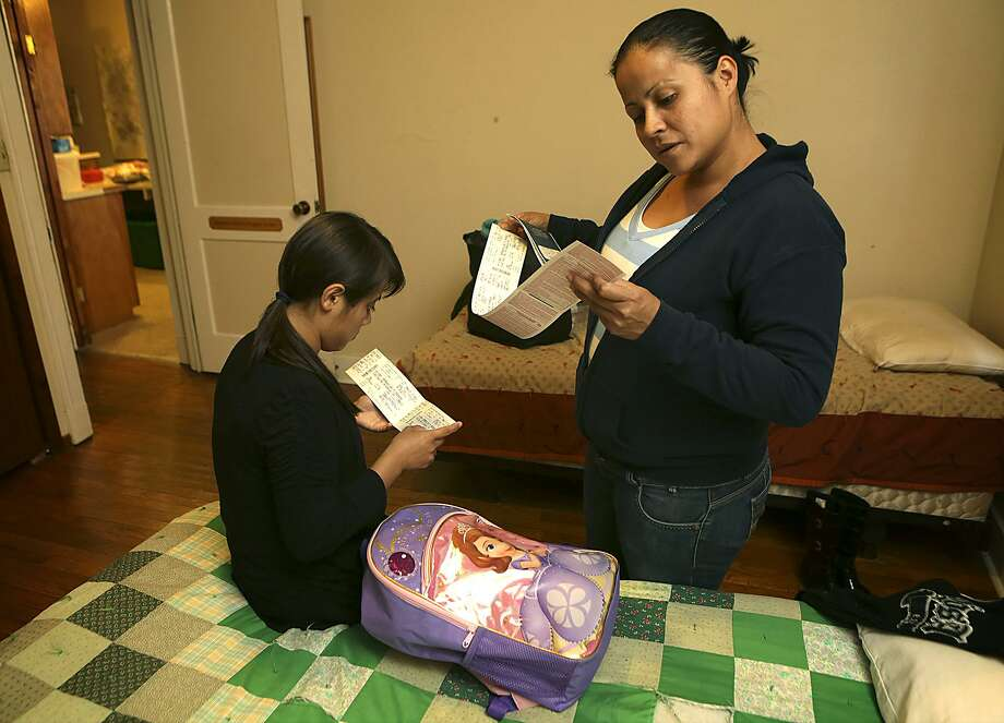 Yeni Artiga, 31, right, of El Salvador, looks over bus tickets to Denver with her 13 year-old daughter Jhoselin Artiga as they pack their bags for the trip to join Yeni's brother in Colorado.  The Mennonite House in San Antonio is housing immigrants that have been release from detention centers in Dilley and Karnes County in South Texas.  The mother and daughter were held in federal detention in Dilley for two weeks. Yeni said they were fleeing the violence in their home country. They stay there until they leave to go to cities where they have family members. Friday, March 27, 2015. Photo: Bob Owen, Staff / San Antonio Express-News / ©2015 San Antonio Express-News
