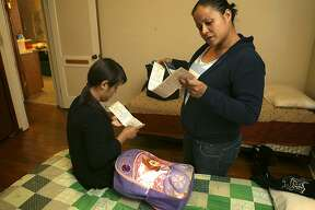 Yeni Artiga, 31, right, of El Salvador, looks over bus tickets to Denver with her 13 year-old daughter Jhoselin Artiga as they pack their bags for the trip to join Yeni's brother in Colorado.  The Mennonite House in San Antonio is housing immigrants that have been release from detention centers in Dilley and Karnes County in South Texas.  The mother and daughter were held in federal detention in Dilley for two weeks. Yeni said they were fleeing the violence in their home country. They stay there until they leave to go to cities where they have family members. Friday, March 27, 2015.