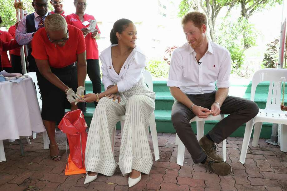 Prince Harry watches as Singer Rihanna gets her blood sample taken for an live HIV test, in order to promote more widespread testing for the public at the 'Man Aware' event held by the Barbados National HIV/AIDS Commission on the eleventh day of an official visit on Dec. 1, 2016 in Bridgetown, Barbados.  Prince Harry's visit to The Caribbean marks the 35th Anniversary of Independence in Antigua and Barbuda and the 50th Anniversary of Independence in Barbados and Guyana.  (Photo by Chris Jackson - Pool/Getty Images) Photo: Chris Jackson, Staff / 2016 Getty Images