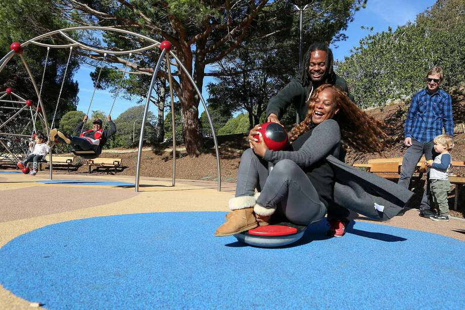 Longtime residents Rodney Sanford Jr. (center back) and Wendy Buler have as much fun as the kids trying out the newly refinished Hilltop Park playground. Photo: Amy Osborne, Special To The Chronicle