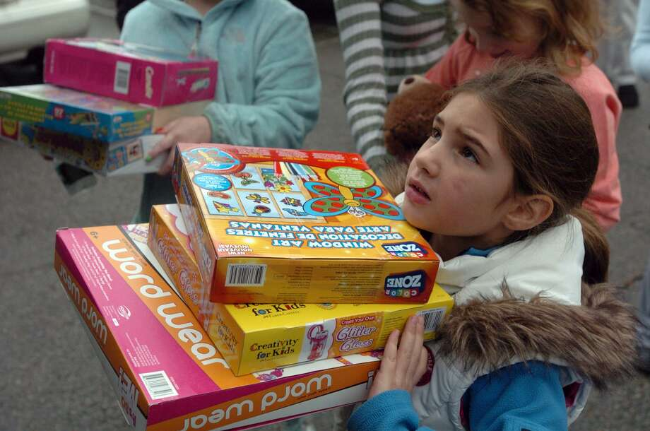 Seen here in 2012, Lena Natale, 6, helps load a truck for the Toys for Tots annual toy drive at the Banksville Community House. The 2016 collection will again be in Banksville and Cos Cob and will take place on Dec. 10. Photo: Keelin Daly / Keelin Daly / Stamford Advocate Riverbend Stamford, CT