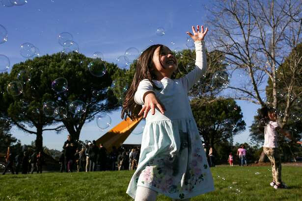 Neighborhood children chase after bubbles at the Hilltop Park ribbon cutting ceremony near the iconic sundial in the Bayview neighborhood on Saturday, December 3, 2016.