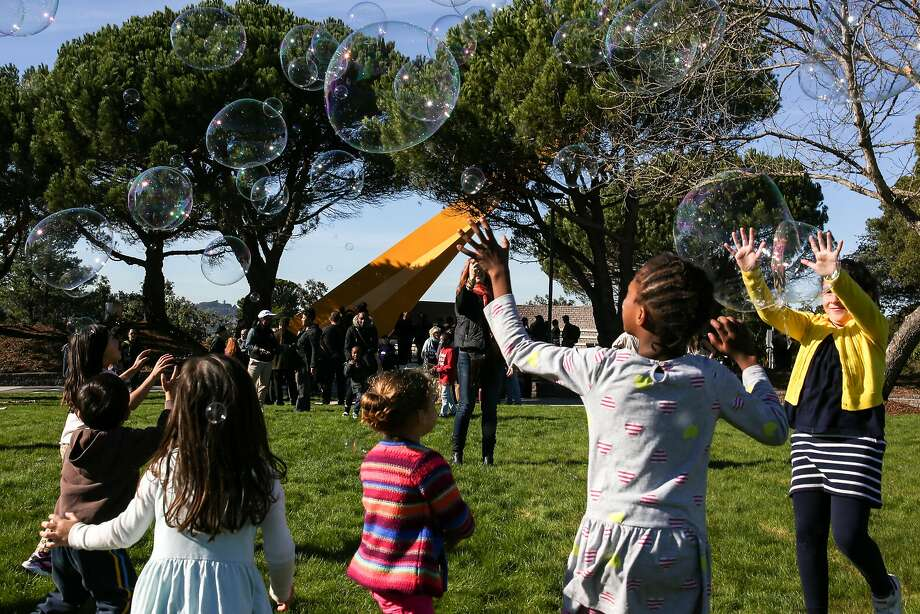 Neighborhood children chase after bubbles at the Hilltop Park ribbon cutting ceremony near the iconic sundial in the Bayview neighborhood on Saturday, December 3, 2016. Photo: Amy Osborne, Special To The Chronicle
