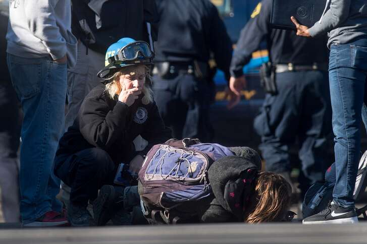 A man collapses on the ground while speaking with emergency personnel at the scene of a fire that killed at least nine people in Oakland on Saturday, Dec. 3, 2016.