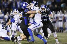 Darien defensive end Mark Evanchick (90) and teammate Quinlin Fay (83) take down Southington quarterback Jasen Rose (20) in the CIAC high school football tournament semifinal game between No. 2 Darien and No. 3 Southington at Boyle Stadium in Stamford, Conn. Monday, Dec. 7, 2015.