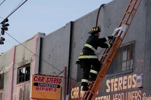 An Oakland firefighter climbs a latter to survey a fatal fire where at least nine people died in a warehouse party on 31st Avenue in Oakland, Calif., on Saturday, Dec. 3, 2016. (Ray Chavez/Bay Area News Group/TNS)