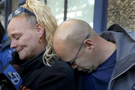 Kim Gregory and her husband David Gregory, Sr. embrace while they wait for updates at an Alameda County Sheriff's office on the fate of their daughter Michela Gregory in Oakland, Calif. on Saturday, Dec. 3, 2016 after at least nine people died and several others are unaccounted for in an overnight fire.