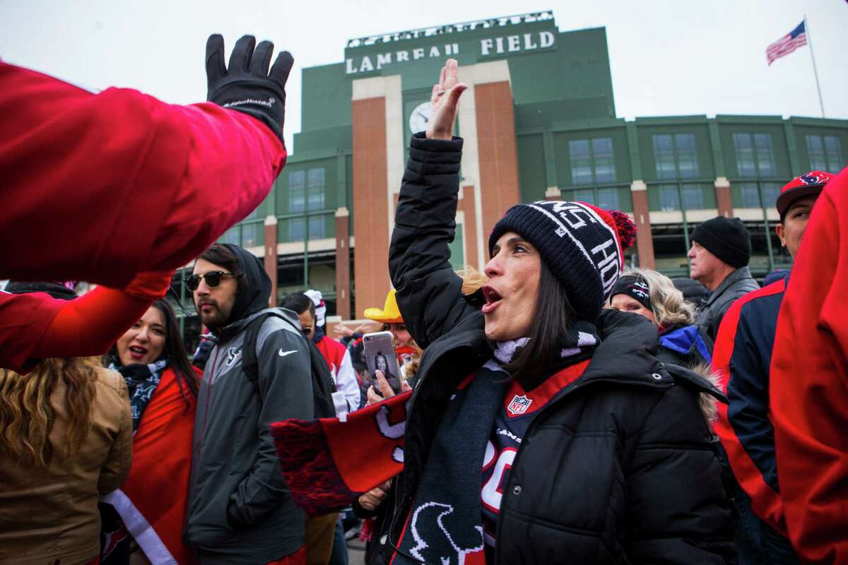 Houston Texans fan Peggy Pound high fives other fans outside Lambeau Field before gathering for a group photo on Saturday, Dec. 3, 2016, in Green Bay, Wis. The Texans face the Green Bay Packers on Sunday inside the historic stadium.