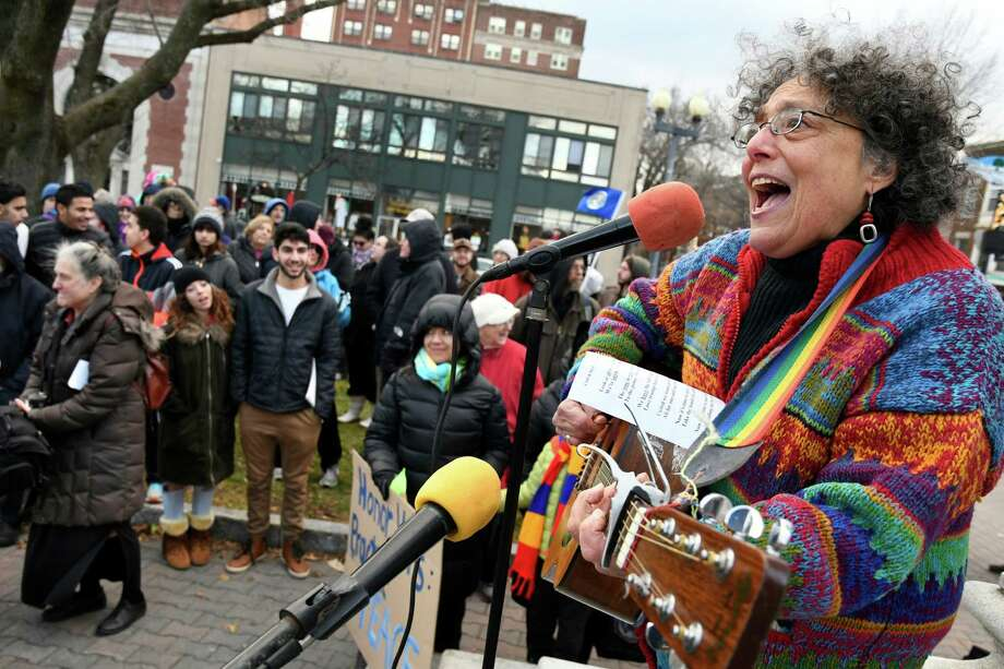 """Ruth Pelham of Albany, right, plays her song """"Look to the People"""" during a rally to denounce hate and embrace diversity on Saturday, Dec. 3, 2016, at Townsend Park in Albany, N.Y. The Capital District Coalition Against Islamophobia held the rally in response to the Ku Klux Klan's victory parade in North Carolina to celebrate President-elect Donald Trump's win. (Cindy Schultz / Times Union) Photo: Cindy Schultz / Albany Times Union"""