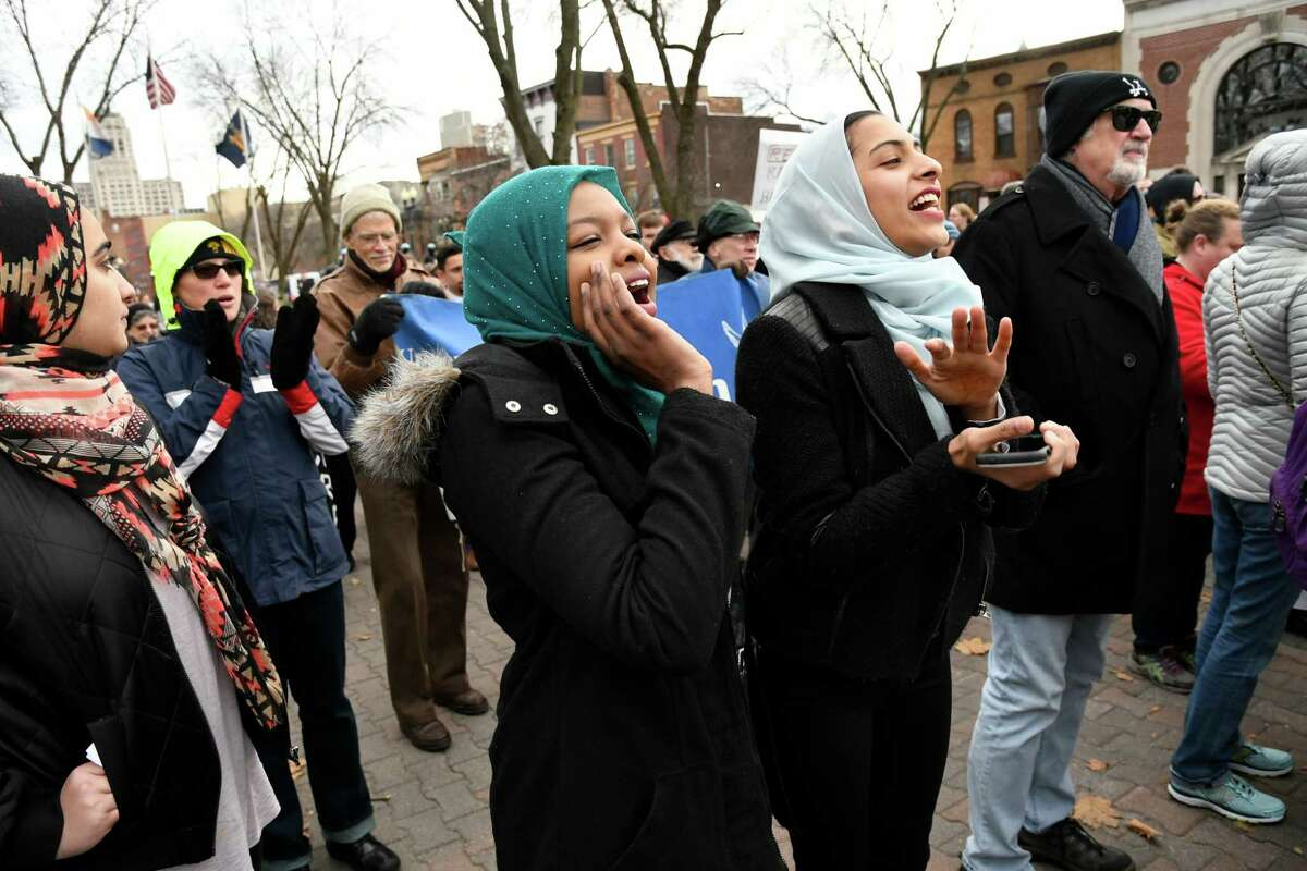 Esra Dawood, vice president of Siena College Muslim Student Assoc., center, and her friend Sara Khan cheer on speakers during a rally to denounce hate and embrace diversity on Saturday, Dec. 3, 2016, at Townsend Park in Albany, N.Y. The Capital District Coalition Against Islamophobia held the rally in response to the Ku Klux Klan's victory parade in North Carolina to celebrate President-elect Donald Trump's win. (Cindy Schultz / Times Union)