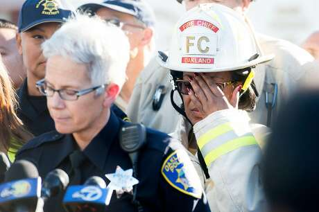 Oakland Fire Chief Fire Teresa Deloach Reed covers her face during a press conference at the scene of a fatal fire in Oakland, Calif., on Saturday, Dec. 3, 2016.