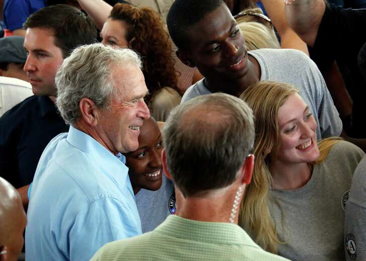 "Former President George W. Bush takes a ""selfie"" with a group of AmeriCorps volunteers during a salute to first responders of Hurricane Katrina in last August in Gulfport, Miss."