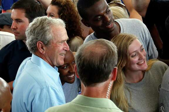 """Former President George W. Bush takes a """"selfie"""" with a group of AmeriCorps volunteers during a salute to first responders of Hurricane Katrina in last August in Gulfport, Miss."""