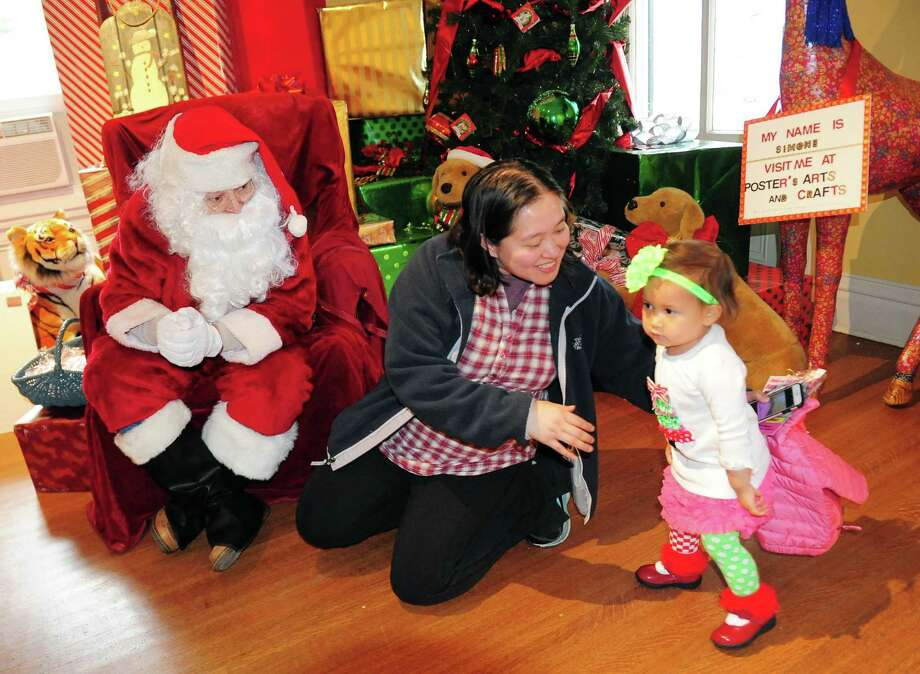 """Khristine Bauer, of Fairfield, tries to coax her daughter Alice, 1, over to visit Santa during the 31st Annual """"A Visit to Santa's House"""" held at the historic Burr Homestead in Fairfield, Conn. on Saturday Dec. 3, 2016. Some of the activities include holiday art & crafts, a bake sale, face painting, performances by Flash Pointe Dance and much more. The event continues Sunday from 10 am to 2 pm. The Junior Women's Club of Fairfield host the event along with sponsor Newman's Own. Proceeds to benefit Healing Tree Economic Development. Photo: Christian Abraham / Christian Abraham / Connecticut Post"""