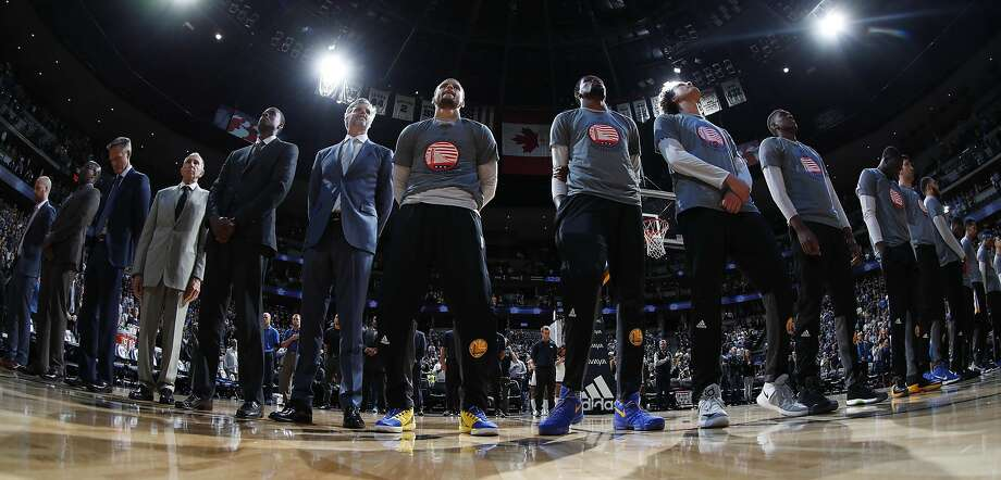 Golden State Warriors guard Stephen Curry (30), center left, and Golden State Warriors forward Kevin Durant (35) center right, stand with teammates during the playing of the National Anthem before facing the Denver Nuggets in the first half of an NBA basketball game Thursday, Nov. 10, 2016, in Denver. (AP Photo/David Zalubowski) Photo: David Zalubowski, Associated Press
