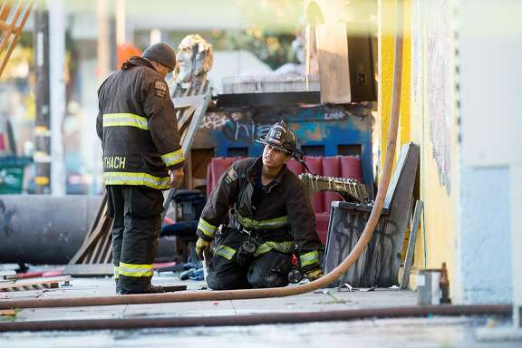 Firefighters work at the scene of a fire that killed at least nine people on 31st Ave. in Oakland, Calif., on Saturday, Dec. 3, 2016.