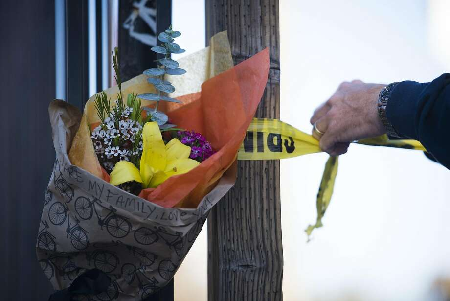 "A law enforcement officer removes police line tape from a post near some flowers at the scene of a fire near 31st Avenue and International Boulevard on December 3, 2016 in Oakland, California. ""You are my family, love you!"" is written on the bouquet. Photo: Pete Kiehart, Special To The Chronicle"