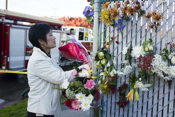 An Oakland resident, who wished not to be identified, leaves a bouquet of flowers at the scene of a fire near 31st Avenue and International Boulevard on December 3, 2016 in Oakland, California.