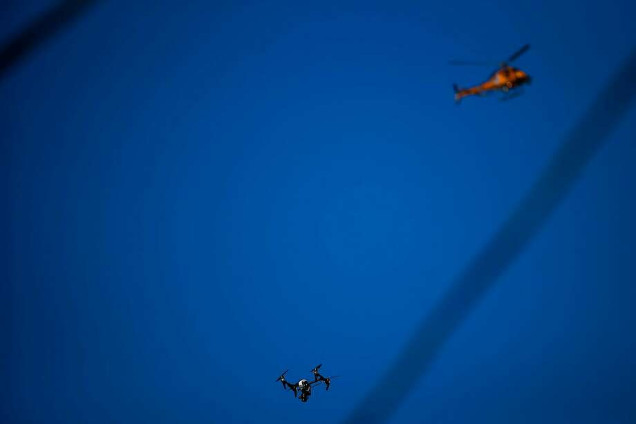 A drone flies close to a helicopter in Oakland in December. A similar close call in Petaluma impeded fire operations, officials say. Photo: Pete Kiehart, Special To The Chronicle
