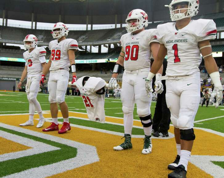 Members of The Woodlands High School football team carry the jersey of linebacker Grant Milton (21), who was named an honorary captain, before a Division I Region II-6A final game against Round Rock at McLane Stadium Saturday, Dec. 3, 2016, in Waco. Milton suffered a serious head injury during the team's Nov. 26 win over Austin Bowie in a UIL Class 6A Division I regional semifinal playoff game at Baylor's McLane Stadium. He was taken to a Waco hospital to have emergency surgery where he remains in a medically induced coma.