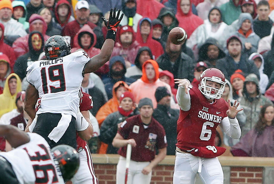 OU quarterback Baker Mayfield, right, torched Oklahoma State with his arm Saturday and afterward declared he's returning next year for a title three-peat bid. Photo: Alonzo Adams, FRE / FR159426 AP