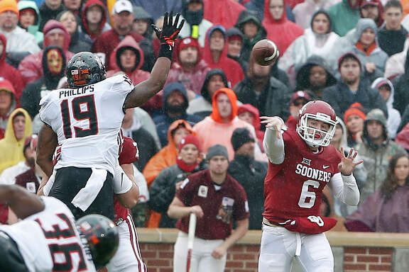 OU quarterback Baker Mayfield, right, torched Oklahoma State with his arm Saturday and afterward declared he's returning next year for a title three-peat bid.