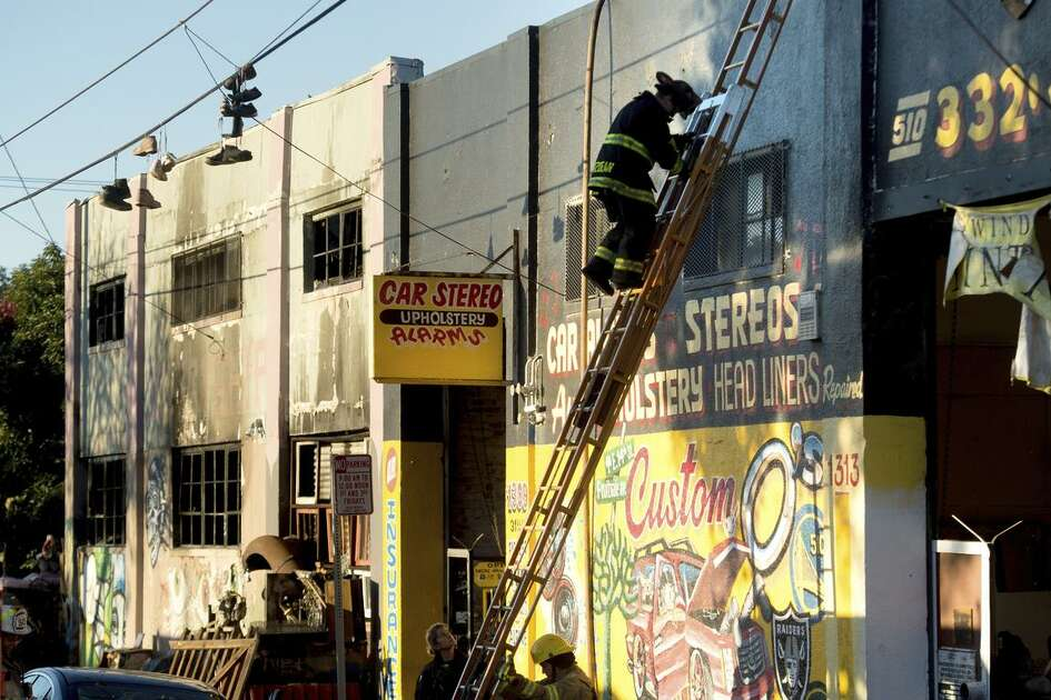 Firefighters check the condition of the Oakland building where a Friday night blaze killed partygoers. The ware house had been the subject of complaints.