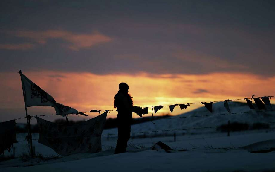 A woman watches the sunset at the Oceti Sakowin camp where people continue to protest the Dakota Access oil pipeline in Cannon Ball, N.D., despite an evacuation order and frigid temperatures. Photo: David Goldman, STF / Copyright 2016 The Associated Press. All rights reserved.