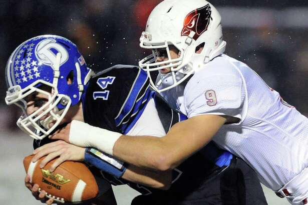At left, Darien quarterback Brian Peters (14) is sacked by Ian Pearson (9) of Greenwich during the Class LL playoff game between Greenwich and Darien at Stamford High School on Nov. 29.
