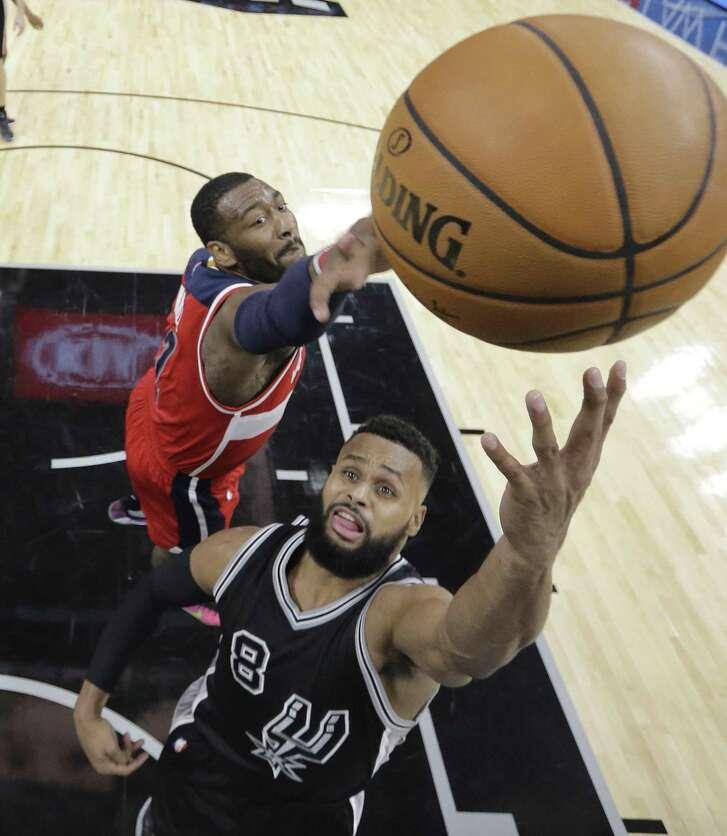 San Antonio Spurs guard Patty Mills (8) shoots past Washington Wizards guard John Wall (2) during the second half of an NBA basketball game, Friday, Dec. 2, 2016, in San Antonio. San Antonio won 107-105. (AP Photo/Eric Gay)