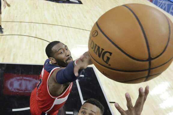San Antonio Spurs guard Patty Mills (8) shoots past Washington Wizards guard John Wall (2) during the second half of an NBA basketball game, Friday, Dec. 2, 2016, in San Antonio. San Antonio won 107-105. (AP Photo/Eric Gay)