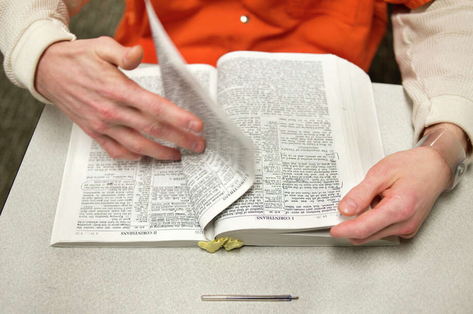 BRITTNEY LOHMILLER | blohmiller@mdn.net Midland County Jail inmate Andrew Cloud Furman flips to a Bible passage to read during Bible study at the jail Tuesday evening. Chaplain Bill LaClaire and volunteers lead a worship service on Sundays and Bible studies during the week.