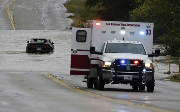 Rescue crews helped a driver and a passenger out of a Ford Mustang that became stuck in high water from a creek along West Commerce and Pinn Road on Saturday, Dec. 3, 2016. Weather forecasts have called for continued rain storms in the area through the weekend. The two individuals were safely extracted from the vehicle and were treated at the location. (Kin Man Hui/San Antonio Express-News)