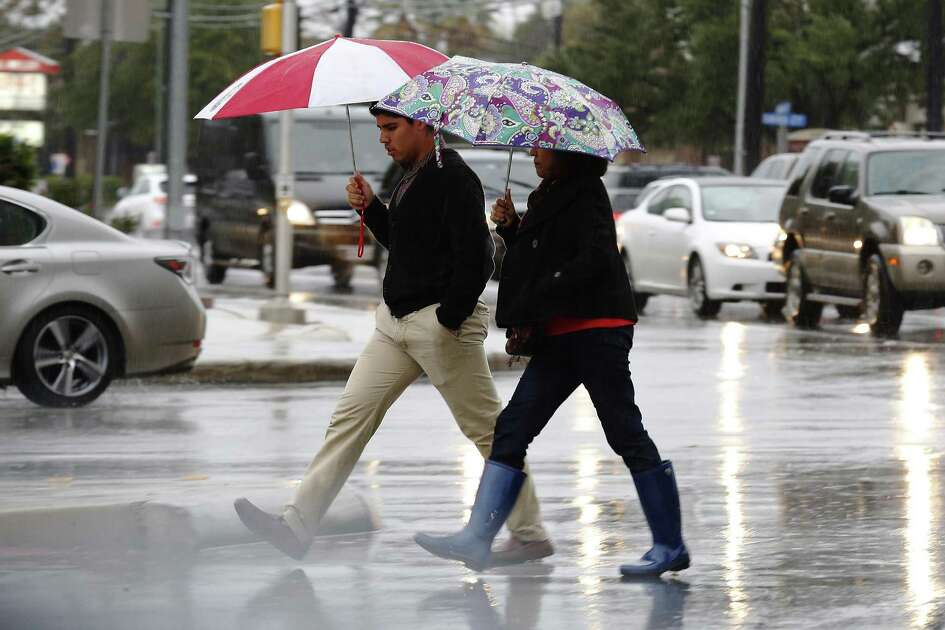 Two individuals cross the intersection of Broadway and Hildebrand as rain storms came down the entire day on Saturday, Dec. 3, 2016. The deluge caused rivers, streams and creeks to swell as first responders ran on calls to help people who drove their vehicles into the flooded waters.  Weather forecasts have called for continued rain storms in the area through the weekend. (Kin Man Hui/San Antonio Express-News)